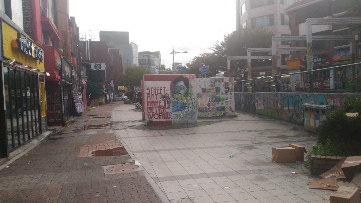 A foto mostra muros em forma de placas quadradas com graffittis  ocupando uma praça em Hongdae,