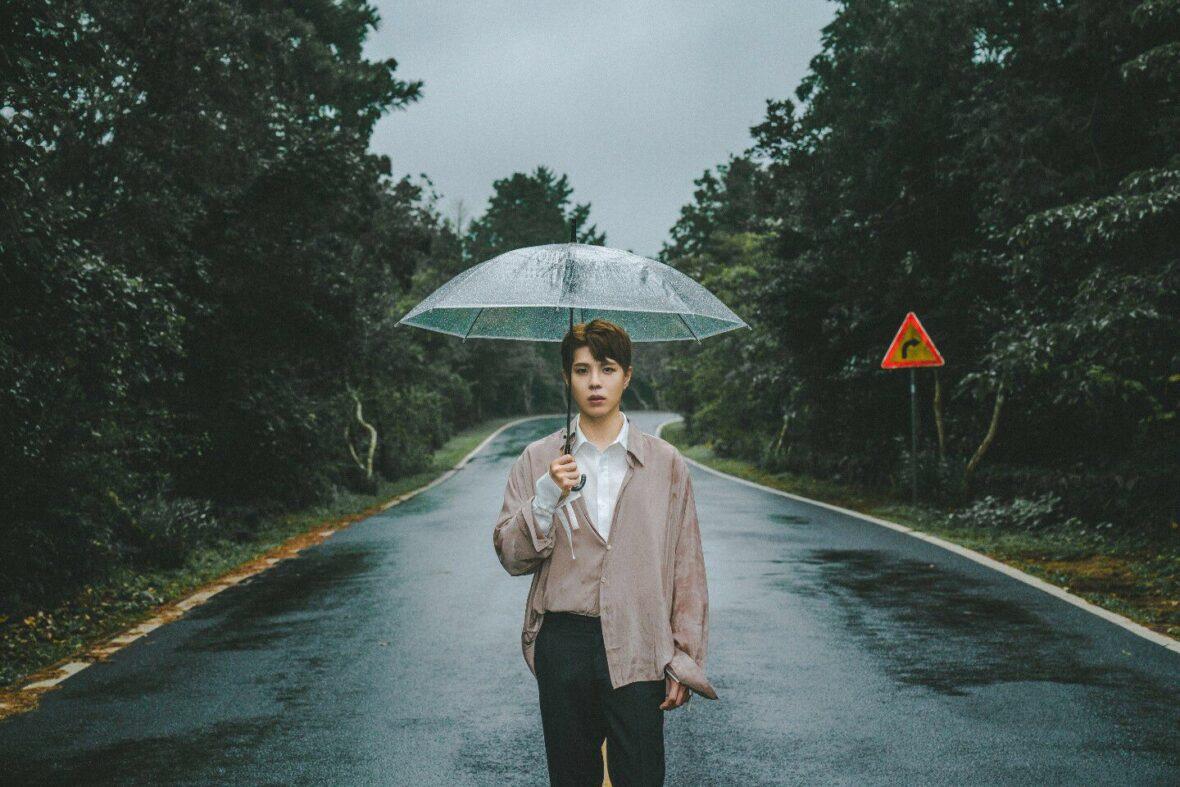 KISU parado em uma estrada com guarda-chuva aberto